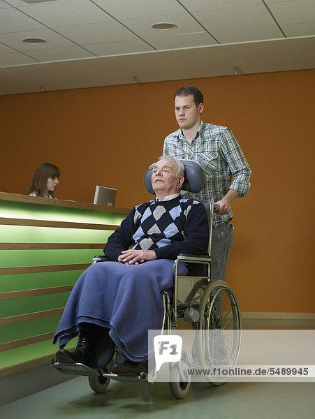 Mann schiebt älteren Mann im Rollstuhl