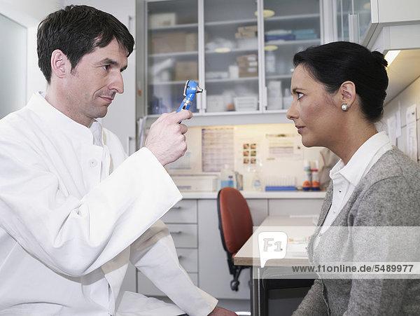 Deutschland  Hamburg  Arzt bei der Augenuntersuchung mit Otoskop