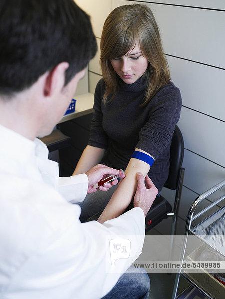 Deutschland  Hamburg  Arzt injizierender Patient in der Klinik