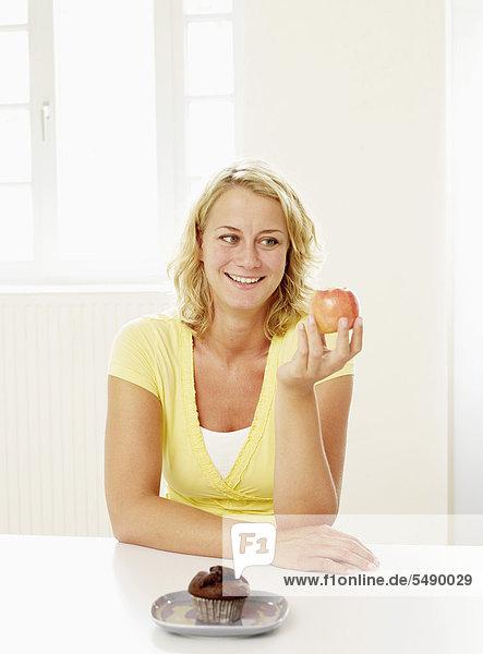 Mittlere erwachsene Frau entscheidet sich zwischen Muffin und Apfel