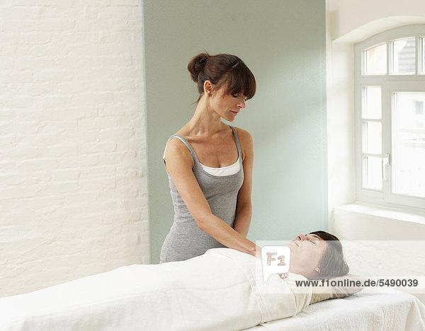 Frau erhält Reiki-Behandlung von Masseurin