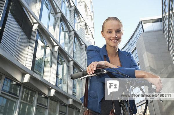 Teenage girl on bicycle  smiling  portrait