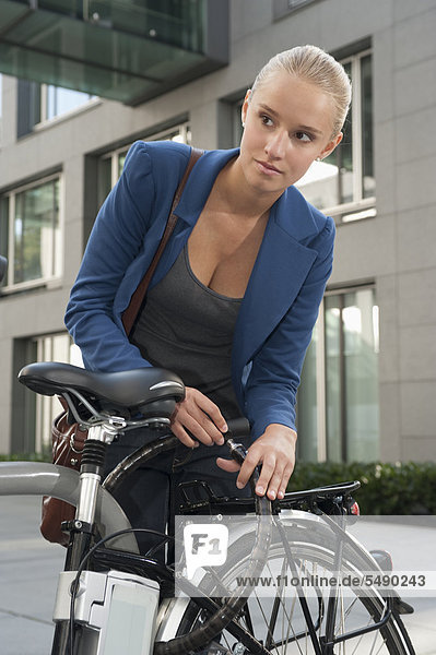 Teenage girl fixing lock of bicycle