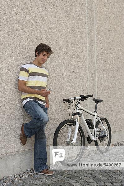 Junger Mann beim Telefonieren mit dem Fahrrad  lächelnd