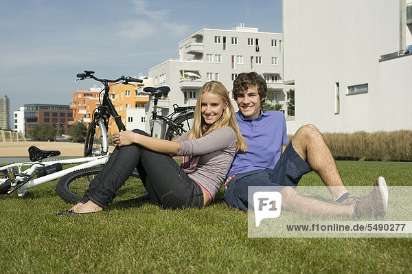 Germany  Bavaria  Couple sitting in grass  smiling  portrait
