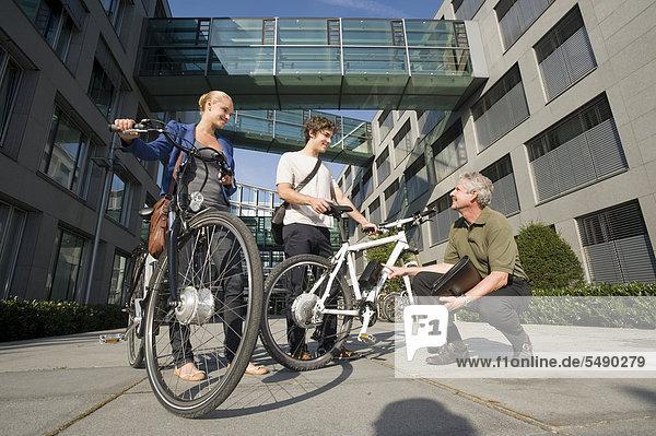 Deutschland  Bayern  Menschen mit Zyklus diskutieren gemeinsam  lächelnd