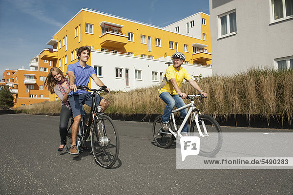Man riding bicycle and girl sitting back  smiling