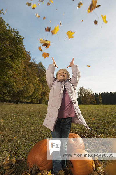 Girl playing with leaves  smiling
