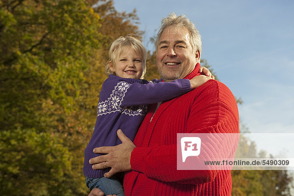 Germany  Bavaria  Grandfather carrying granddaughter  smiling  portrait