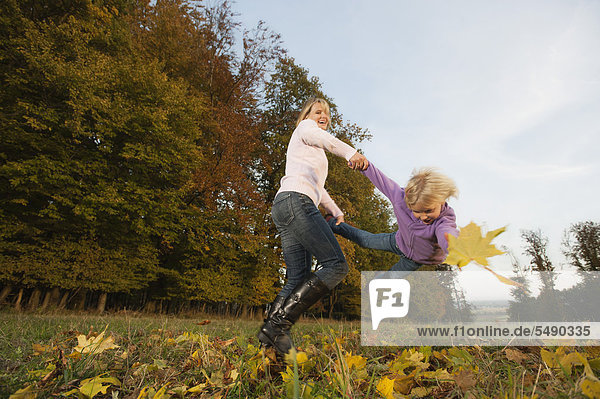 Germany  Bavaria  Mother and daughter playing during autumn