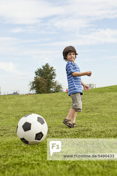 Boy playing with soccer ball in park