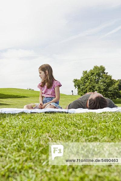 Girl looking away  father lying on blanket