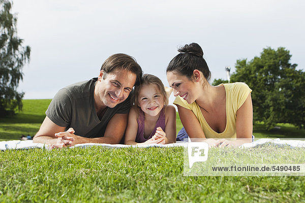 Germany  Bavaria  Family lying on blanket in park  smiling
