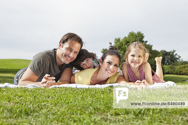 Germany  Bavaria  Family lying on blanket in park  smiling  portrait