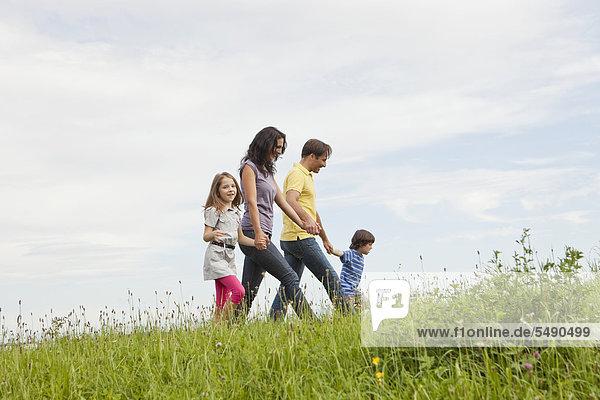 Deutschland  Bayern  Familie beim Graswandern im Park