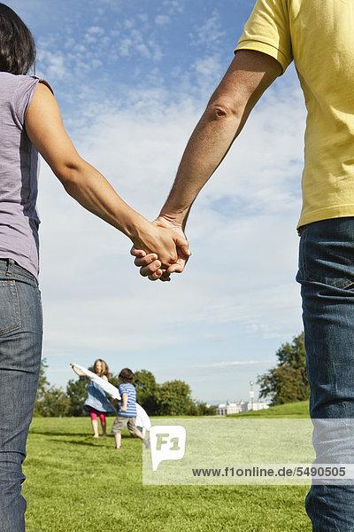 Deutschland  Bayern  Eltern halten Händchen  während Kinder im Hintergrund im Park spielen