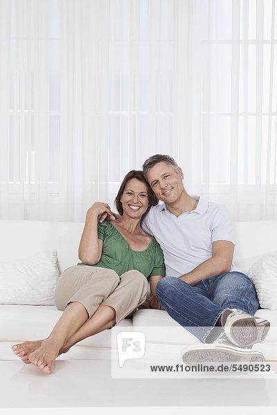 Deutschland  München  Paar auf Couch sitzend  lächelnd  Portrait