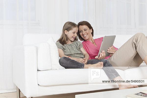Deutschland  München  Mutter und Tochter mit digitalem Tablett  lächelnd