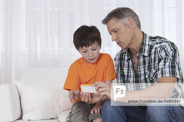 Deutschland  München  Sohn und Vater spielen mit dem Handy