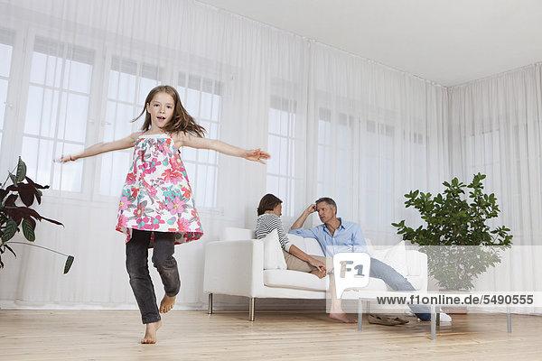 Eltern sitzend auf der Couch  Mädchen spielend