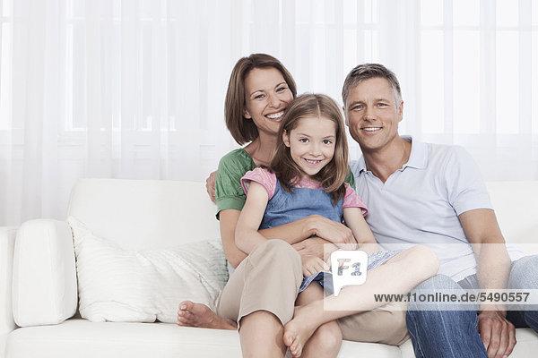 Deutschland  München  Familie auf Couch sitzend  lächelnd  Portrait