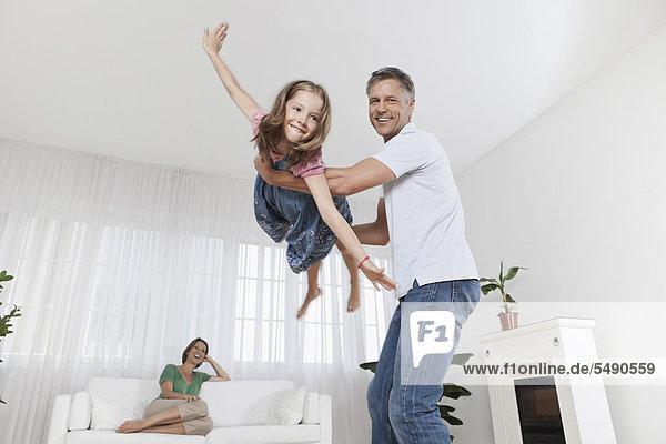 Deutschland  München  Vater spielt mit Tochter  Mutter im Hintergrund