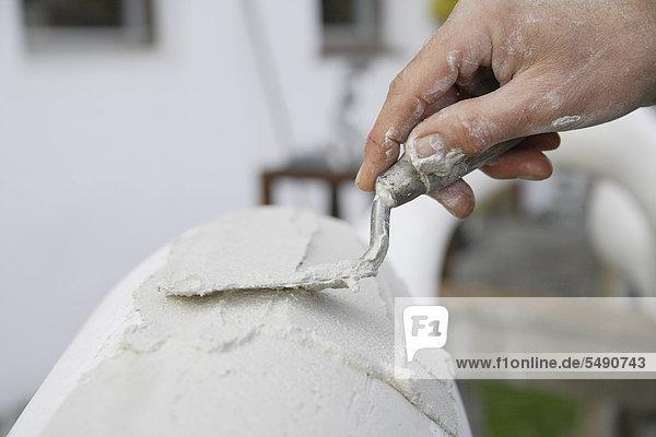 Germany  Upper Bavaria  Munich  Schaeftlarn  Sculptor applying plaster with trowel