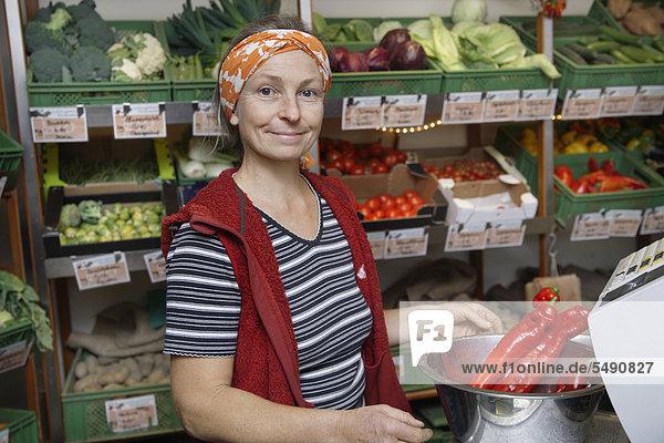 Deutschland  Oberbayern  Wolfratshausen  Reife Frau mit roter Chilischote im Geschäft  lächelnd  Portrait
