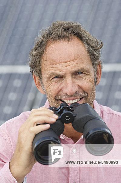Erwachsener Mann hält Fernglas in Solaranlage  lächelnd  Portrait