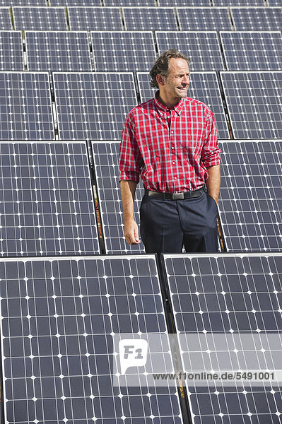 Reifer Mann in Solaranlage stehend  lächelnd