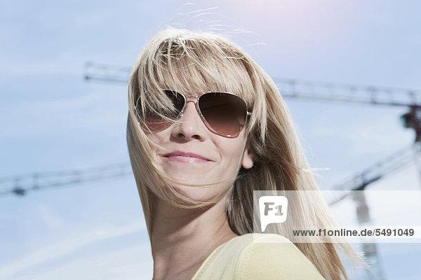 Junge Frau mit Sonnenbrille  lächelnd