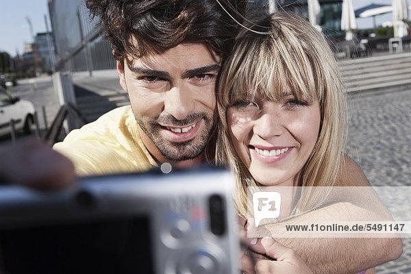 Deutschland  Köln  Junges Paar mit Handy zum Fotografieren  lächeln