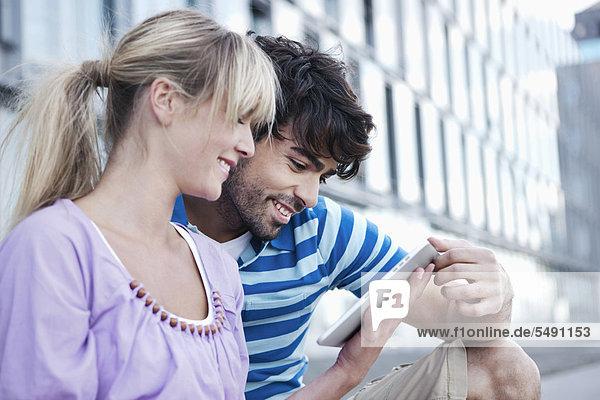 Deutschland  Köln  Junges Paar mit digitalem Tablett  lächelnd