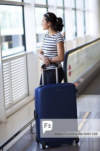 Frau mit Koffer wartet am Flughafen