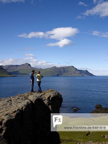 Couple standing on cliff  Skalanes  Eastern  Iceland