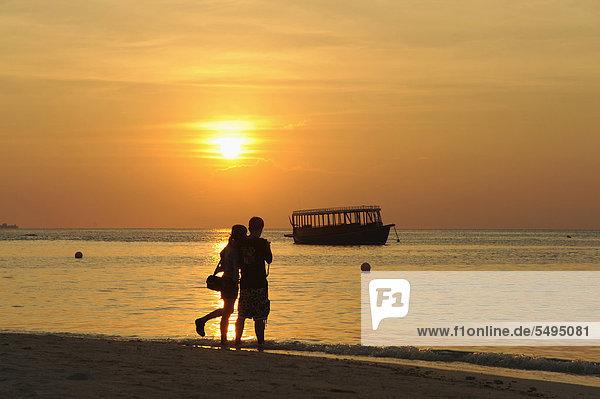 Pärchen am Strand einer Malediveninsel bei Sonnenuntergang  Malediven  Indischer Ozean