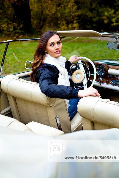 Junge Frau vor einem Mercedes aus der Nachkriegszeit  Oldtimer