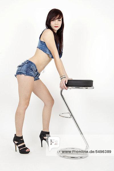 Junge Frau posiert selbstbewusst in kurzen Hotpants  BH und High Heels