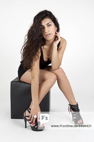 Junge Frau im schwarzen Top  Hotpants und High Heels posiert mit schwarzem Würfel