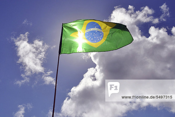 Brazilian national flag against a blue sky with clouds  South America