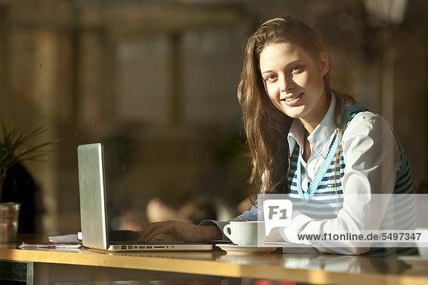 Studentin mit Laptop sitzt in Cafe  durch Fensterscheibe gesehen