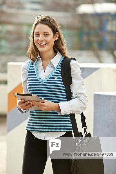 Studentin mit Tablet-PC und Umhängetasche unterwegs