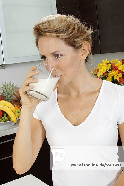 Woman In Kitchen Drinking Milk
