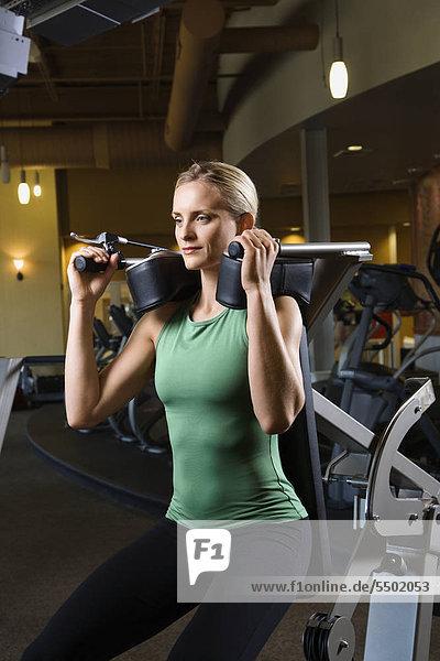 Erstklassige Erwachsenen Caucasian Frau mit Übungs-Ausrüstung an der Gymnastik.