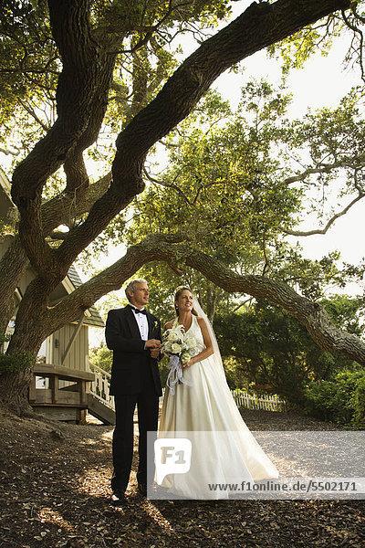 Mid-adult Bride and Groom außerhalb der Kirche stehen.