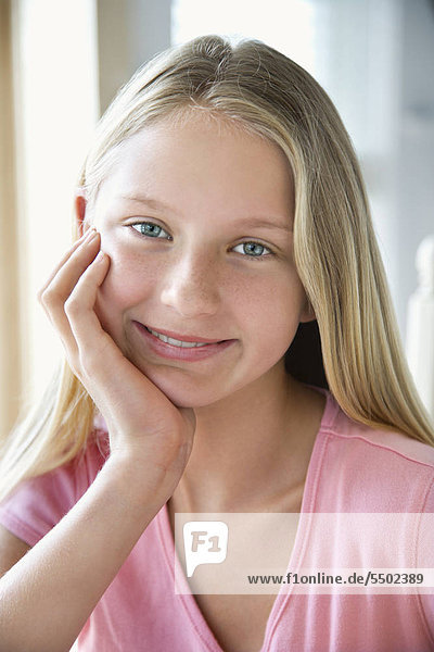 Portrait of Caucasian pre-teen girl looking at viewer resting chin in hand and smiling.