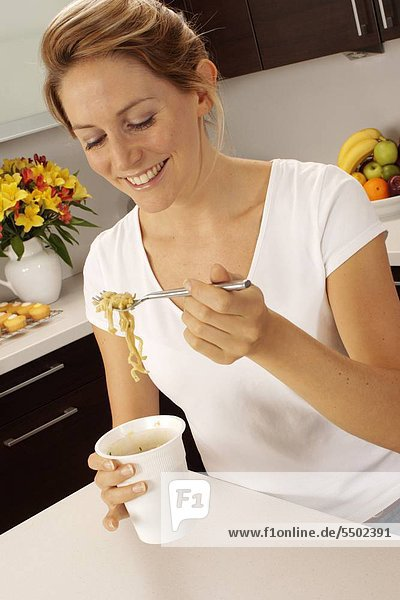 Woman In Kitchen Eating Pot Noodle