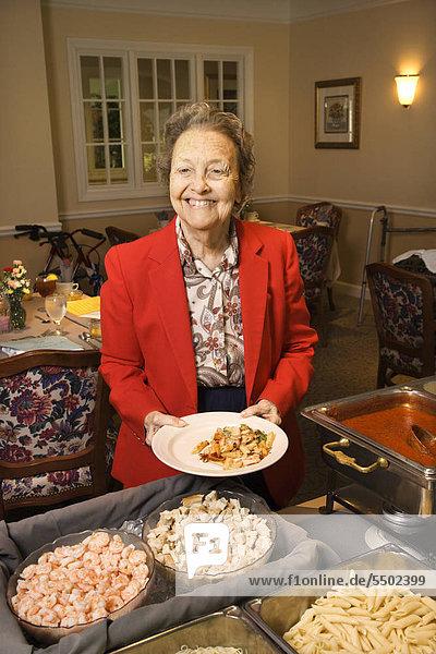 Altlantik Caucasian Frau am Buffet im Speisesaal ein Ruhestand Gemeindehalle.