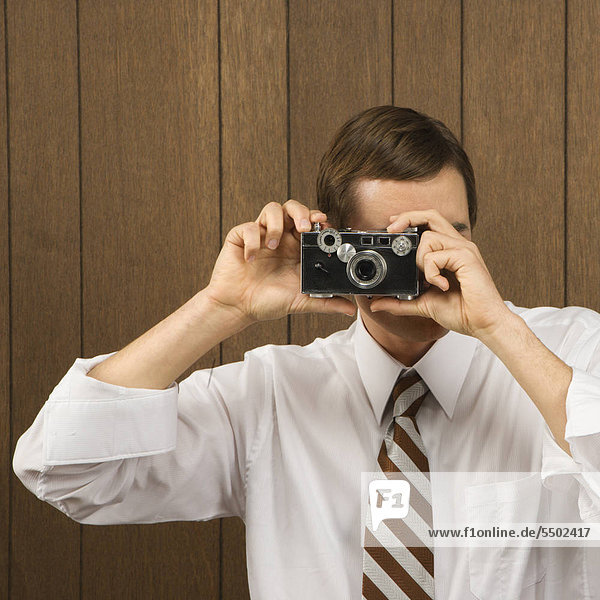 Mid-adult Caucasian male holding vintage camera up to his face.