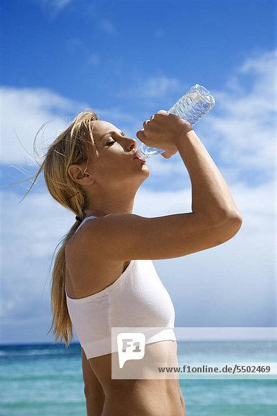 Caucasian young adult woman ärztin Trinkwasser am Strand.